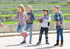 Little girl jumping while jump rope game. With friends outdoor Royalty Free Stock Photography