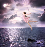 Little girl jumping into the night sky Royalty Free Stock Photos