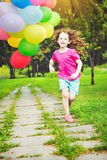Little girl jumping outdoors with balloons. Royalty Free Stock Photos