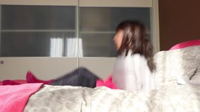 Little girl jumping on parents bed stock footage