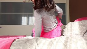 Little girl jumping on parents bed stock video