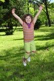 Little girl jumping in park Stock Photo