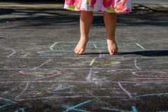 Little girl jumping and playing hopscotch Stock Photo