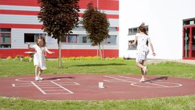 Girl playing hopscotch. Little girl jumping while playing Hopscotch at park. Cute girls on children playground outdoors. Legs of kids jumps hopscotch on asphalt stock video footage