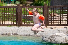 Little girl jumping into the pool. Child jumps into the pool with water Royalty Free Stock Photos
