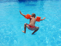 Little girl jumping into the pool Stock Images