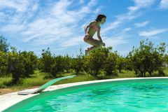 Little girl jumping in pump in an outdoor pool. Between fields of crops in Sicily, Italy royalty free stock image