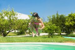 Little girl jumping in pump in an outdoor pool. Between fields of crops in Sicily, Italy royalty free stock photo