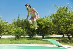Little girl jumping in pump in an outdoor pool. Between fields of crops in Sicily, Italy royalty free stock photos