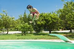 Little girl jumping in pump in an outdoor pool. Between fields of crops in Sicily, Italy stock photos