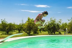 Little girl jumping in pump in an outdoor pool. Between fields of crops in Sicily, Italy stock images