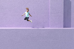 Little girl jumping on purple wall. Royalty Free Stock Photography