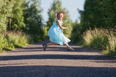 Little girl jumping and rejoicing. On the track Stock Photos