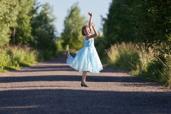 Little girl jumping and rejoicing. On the track Stock Image