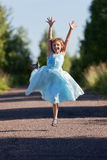 Little girl jumping and rejoicing. On the track Royalty Free Stock Photography