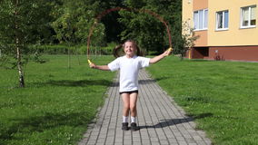 Little girl jumping rope outside stock video footage