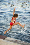 Little girl jumping into the sea. Little caucasian girl jumping into the sea royalty free stock image