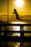Little girl jumping into the sea. Little girl silhouette jumping from 3m springboard into the sea in the summer evening. On background of beautiful sky with royalty free stock photography