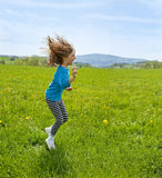 Little girl jumping on spring meadow Royalty Free Stock Photos