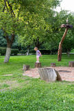 Little girl jumping between stumps in the park Royalty Free Stock Photo