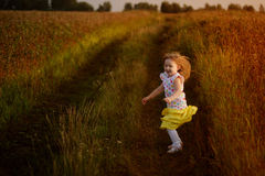 Little girl jumping in a summer field in a good mood emotions Royalty Free Stock Image