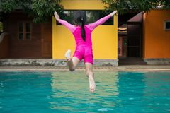 Little girl jumping in swimming pool. Royalty Free Stock Photo