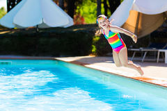 Little girl jumping into swimming pool Royalty Free Stock Images