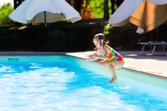 Little girl jumping into swimming pool Stock Photography