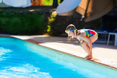 Little girl jumping into swimming pool Stock Images