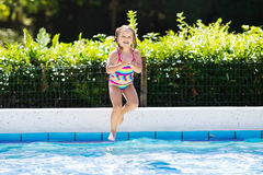 Little girl jumping into swimming pool Royalty Free Stock Photo