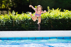 Little girl jumping into swimming pool Royalty Free Stock Photography