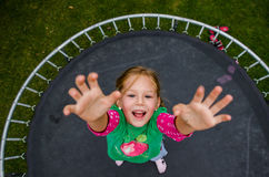 Little girl jumping on trampoline Royalty Free Stock Image