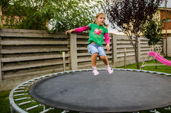 Little girl jumping on trampoline Stock Images