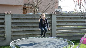 Little girl jumping on trampoline stock footage