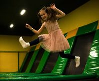 Little girl is jumping on a trampoline in kids play room on her birthday.  stock photo
