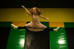 Little girl is jumping on a trampoline in kids play room on her birthday.  royalty free stock image