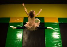 Little girl jumping on a trampoline and making twine split in play room for kids.  royalty free stock photography