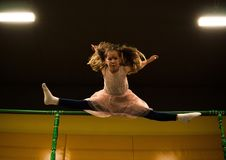 Little girl jumping on a trampoline and making twine split in play room for kids.  royalty free stock photo