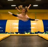 Little girl jumping on a trampoline and making twine split in play room for kids.  royalty free stock photos