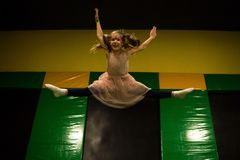 Little girl jumping on a trampoline and making twine split in play room for kids.  royalty free stock images
