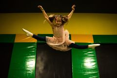 Little girl jumping on a trampoline and making twine split in play room for kids.  stock photo