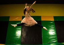 Little girl jumping on a trampoline and making twine split in play room for kids.  stock image