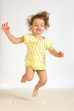 A little girl jumps. A little girl jumps on a bed Stock Image