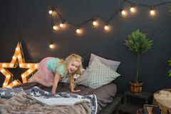 A little girl jumps on a bed. A pretty little girl jumps on a bed Stock Image