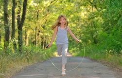 Little girl jumps over rope Stock Photo