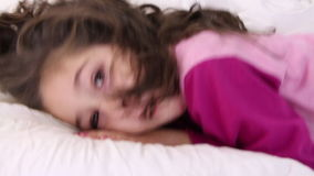 Little girl jumps on a pillow and closes eyes stock video