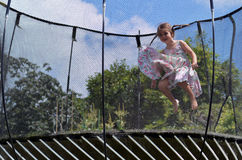Little girl jumps on a trampolin. Happy little girl (age 04) jumps on a trampoline Royalty Free Stock Photos