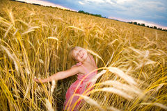 Little girl jumps in a wheat field Royalty Free Stock Image