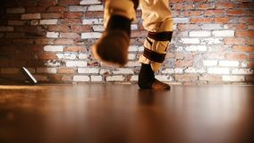 A little girl in karate suit walking throwing up her legs. Warming up. Feet stock video footage