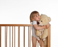 Little girl keeping teddybears in crib Royalty Free Stock Photos